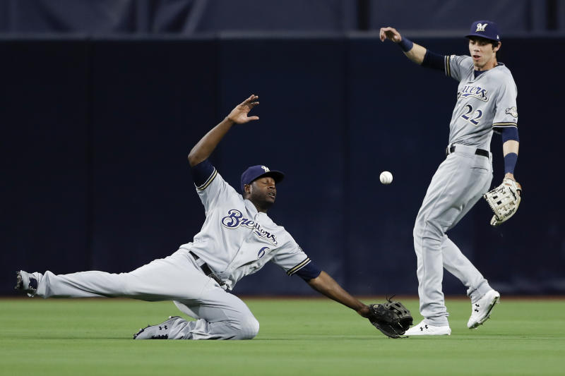Milwaukee Brewers center fielder Lorenzo Cain (6) cannot reach a hit for a double by San Diego Padres' Hunter Renfroe as teammate right fielder Christian Yelich (22) looks on during the third inning of a baseball game Monday, June 17, 2019, in San Diego. (AP Photo/Gregory Bull)
