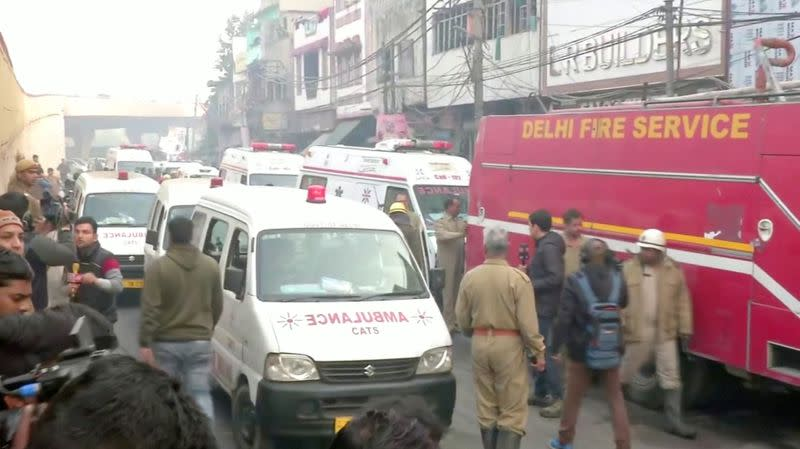 Video grab of ambulences and a firefighting vehicle at the scene of a deadly fire that swept through a factory where laborers were sleeping, in New Delhi