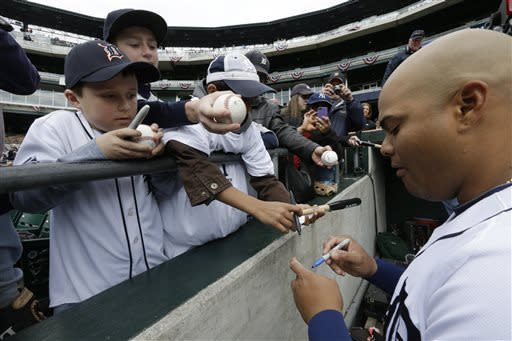 Detroit Tigers catcher Brayan Pena signs autographs before a baseball game against the New York Yankees in Detroit Sunday April 7, 2013. (AP Photo/Carlos Osorio)