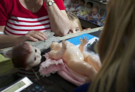 A young customer looks over the counter as a family member brings in a doll for repair at Sydney's Doll Hospital
