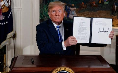 <span>President Donald Trump shows a signed Presidential Memorandum after delivering a statement on the Iran nuclear deal</span> <span>Credit: AP </span>