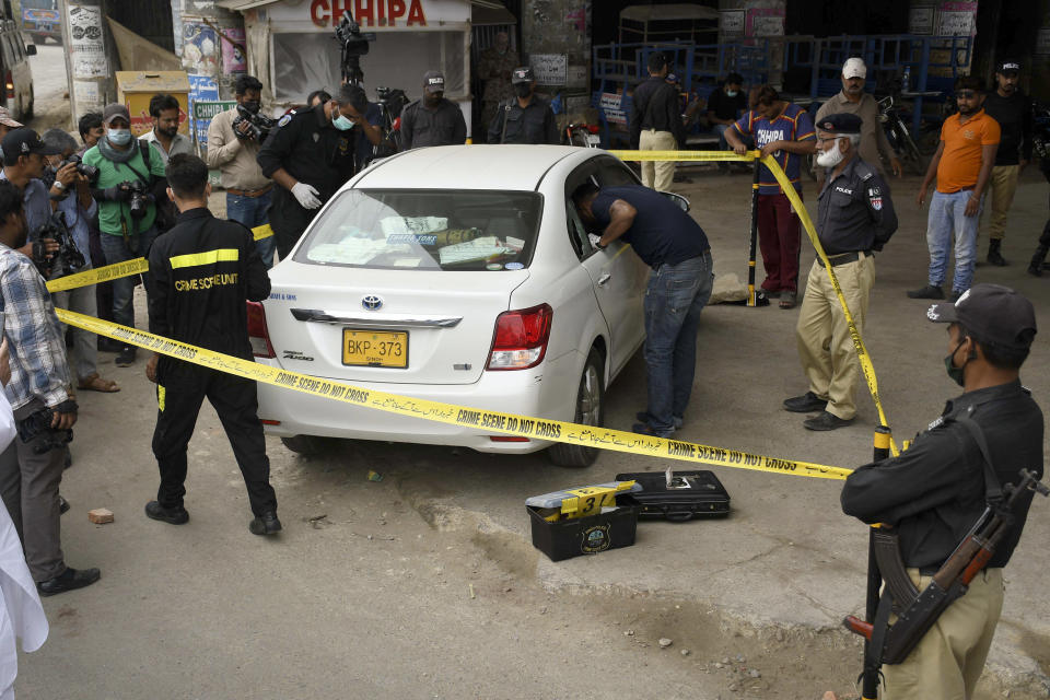 Investigators examine a damaged car at the site of a firing incident, in Karachi, Pakistan, Wednesday, July 28, 2021. Gunmen riding on a motorcycle fired into the car carrying two Chinese factory workers in Pakistan's port city of Karachi on Wednesday, wounding one of them before fleeing the scene, a rescue official and police said. (AP Photo/Fareed Khan)
