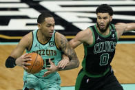 Charlotte Hornets forward P.J. Washington drives to the basket past Boston Celtics forward Jayson Tatum during the first half of an NBA basketball game on Sunday, April 25, 2021, in Charlotte, N.C. (AP Photo/Chris Carlson)