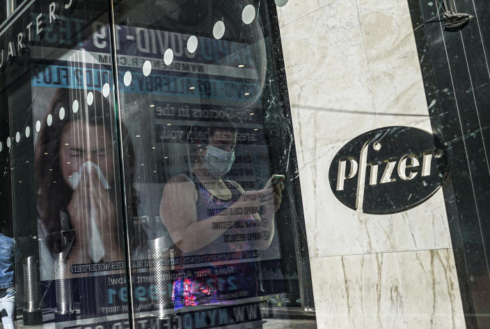 FILE - In this Nov. 9, 2020, an ad for COVID-19 testing reflects on glass at a bus stop, as pedestrians walk past Pfizer world headquarters in New York. (AP Photo/Bebeto Matthews, File)
