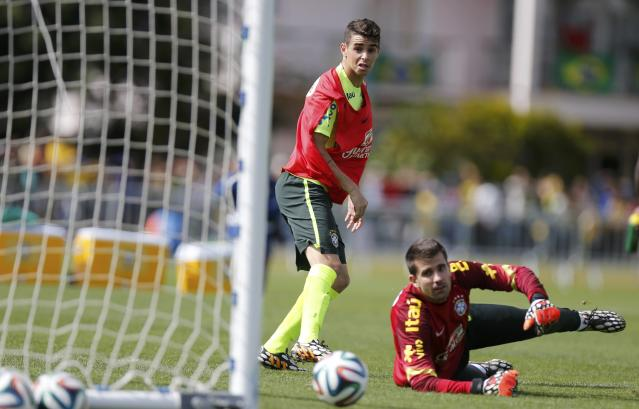 Brazil's Oscar (L) and goalkeeper Victor attend a training session in Teresopolis near Rio de Janeiro July 7, 2014. REUTERS/Marcelo Regua (BRAZIL - Tags: SOCCER SPORT WORLD CUP)