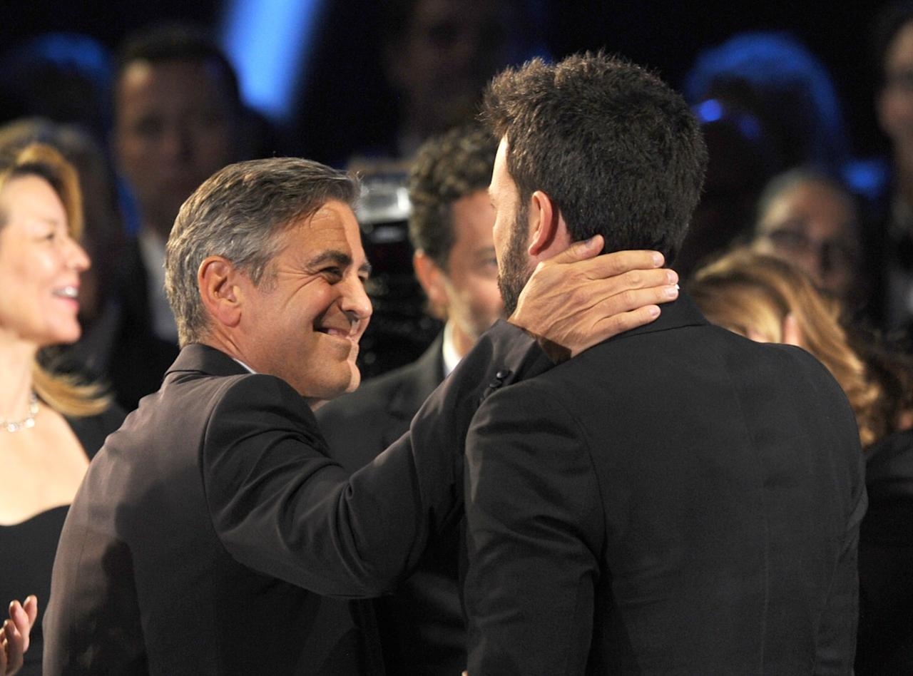"SANTA MONICA, CA - JANUARY 10:  Producer George Clooney (L) hugs actor/Producer/Director Ben Affleck after hearing ""Argo"" won the Best Picture Award at the 18th Annual Critics' Choice Movie Awards held at Barker Hangar on January 10, 2013 in Santa Monica, California.  (Photo by Kevin Winter/Getty Images)"