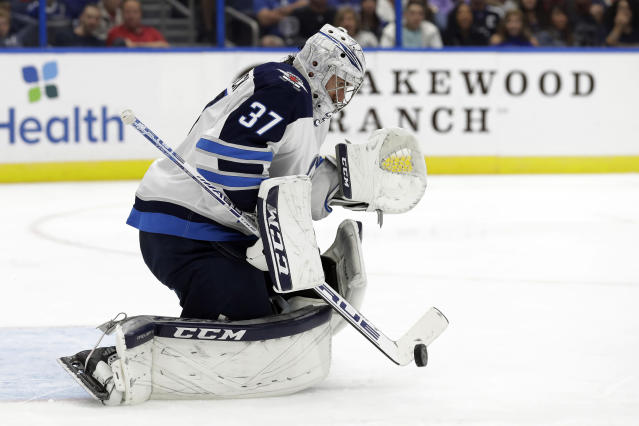 Winnipeg Jets goaltender Connor Hellebuyck (37) makes a save on a shot by the Tampa Bay Lightning during the second period of an NHL hockey game Saturday, Nov. 16, 2019, in Tampa, Fla. (AP Photo/Chris O'Meara)