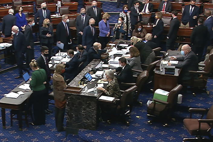 In this image from video, Democratic senators stand as they wait for the announcement that the Senate version of the COVID-19 relief bill has passed by a vote of 50-49 in the Senate at the U.S. Capitol in Washington, Saturday, March 6, 2021. (Senate Television via AP)