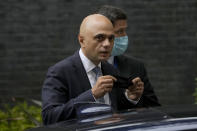 FILE - In this Wednesday, June 30, 2021 file photo, Britain's newly appointed Health Secretary Sajid Javid looks at photographers as he puts on a face mask to curb the spread of coronavirus as he gets into his ministerial vehicle after leaving 10 Downing Street in London. Britain's health secretary said Sunday, Sept. 12, 2021 that authorities have decided not to require vaccine passports for entry into nightclubs and other crowded events in England, reversing course amid opposition from some of the government's supporters in Parliament. (AP Photo/Matt Dunham, File)