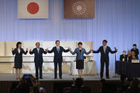 Japanese former Foreign Minister Fumio Kishida, center, celebrates with outgoing Prime Minister Yoshihide Suga, second left, and fellow candidates Seiko Noda, left, Sanae Takaichi, second right, and Taro Kono after winning the Liberal Democrat Party leadership election in Tokyo Wednesday, Sept. 29, 2021. Kishida won the governing party leadership election on Wednesday and is set to become the next prime minister, facing the imminent task of addressing a pandemic-hit economy and ensuring a strong alliance with Washington to counter growing regional security risks. (Carl Court/Pool Photo via AP)
