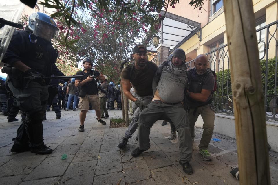 A demonstrator is blocked by plain clothes policemen during clashes broke out between demonstrators and Italian Policemen in riot gears on the occasion of a protest against the G20 Economy and Finance ministers and Central bank governors' meeting in Venice, Italy, Saturday, July 10, 2021. (AP Photo/Luca Bruno)