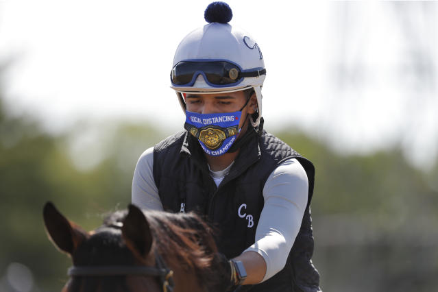 """A riders wearing a mask reading """"Social Distancing World Champion"""" works out a horse at Belmont Park in Elmont, N.Y., Wednesday, June 17, 2020. The 152nd running of the Belmont Stakes is scheduled to be run on Saturday. (AP Photo/Seth Wenig)"""