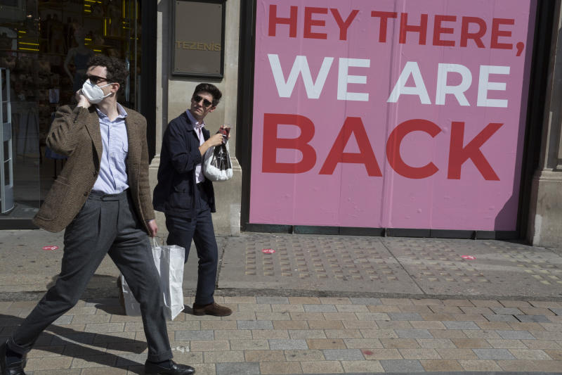 As the UK's Coronavirus lockdown continues to ease, retailers re-open their doors to shoppers, two men walk past the Tenezis shop at Oxford Circus whose window displays the message that they're back, on 18th June 2020, in London, England. (Photo by Richard Baker / In Pictures via Getty Images)