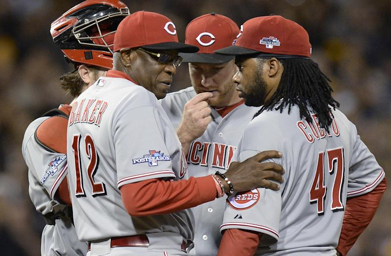 Cincinnati Reds manager Dusty Baker (12) talks with starting pitcher Johnny Cueto on the mound in the fourth inning of the NL wild-card playoff baseball game against the Pittsburgh Pirates on Tuesday, Oct. 1, 2013, in Pittsburgh. (AP Photo/Don Wright)