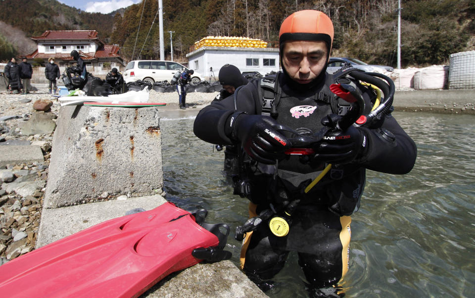 FILE - In this March 9, 2014, file photo, Yasuo Takamatsu prepares to take a diving lesson at Takenoura bay, Miyagi prefecture, northern Japan. Takamatsu, 64, lost his wife, Yuko, when the tsunami hit Onagawa, in Miyagi prefecture. He has been looking for her ever since. He even got his diving license to try to find her remains, and for seven years he has gone on weekly dives. (AP Photo/Koji Ueda, File)
