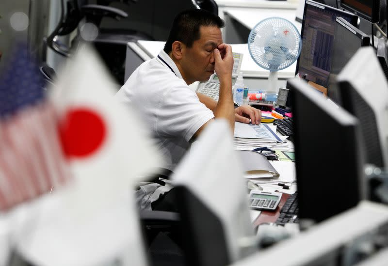 A dealer scratches his face at a foreign exchange trading company in Tokyo