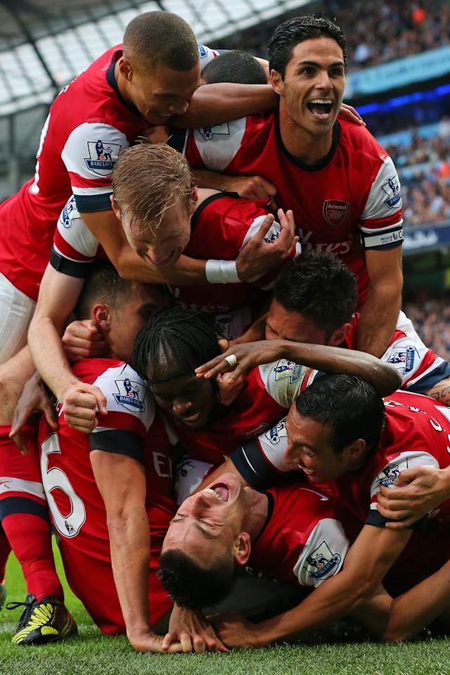 MANCHESTER, ENGLAND - SEPTEMBER 23: Laurent Koscielny of Arsenal is mobbed by his team mates after scoring their first goal during the Barclays Premier League match between Manchester City and Arsenal at Etihad Stadium on September 23, 2012 in Manchester, England. (Photo by Alex Livesey/Getty Images)