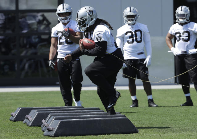 Oakland Raiders running back Marshawn Lynch, center, performs a drill at the NFL football team's facility in Alameda, Calif., Tuesday, April 24, 2018. (AP Photo/Jeff Chiu)