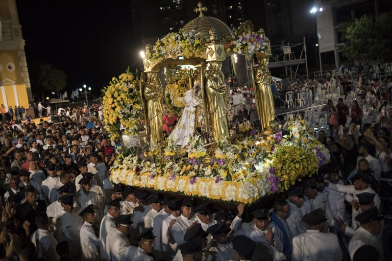 """In this Nov. 18, 2019 photo, faithful referred to as """"Servidores Mañaneros"""" or morning servers, carry the image of the Virgin of Chiquinquira during a procession, in Maracaibo, Venezuela. Thousands of Venezuelans flocking to Maracaibo's ornate basilica each year at this time traditionally ask for help overcoming illness or conceiving a child. But many faithful say a crisis driving the exodus of millions has made them ask for something bigger than themselves. (AP Photo/Rodrigo Abd)"""