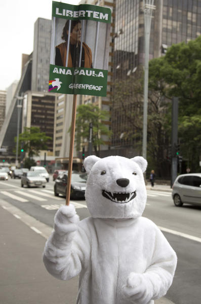 An activist wearing a polar bear costume holds a poster showing Brazilian activist Ana Paula Alminhana Maciel, during a protest in Sao Paulo, Brazil on Saturday, Oct. 5, 2013 demanding the release of the 30 Greenpeace activists detained in Russia. On Thursday, Oct. 3, 2013, Russian investigators charged the entire crew of a Greenpeace ship with piracy for a protest at a Russian oil platform in the Arctic. (AP Photo/Andre Penner)