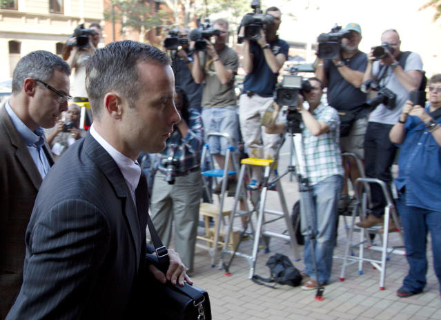 Oscar Pistorius, right accompanied by relative, arrives at the high court in Pretoria, South Africa, Tuesday, March 18, 2014. Pistorius is charged with murder for the shooting death of his girlfriend, Reeva Steenkamp, on Valentines Day in 2013. (AP Photo/Themba Hadebe)