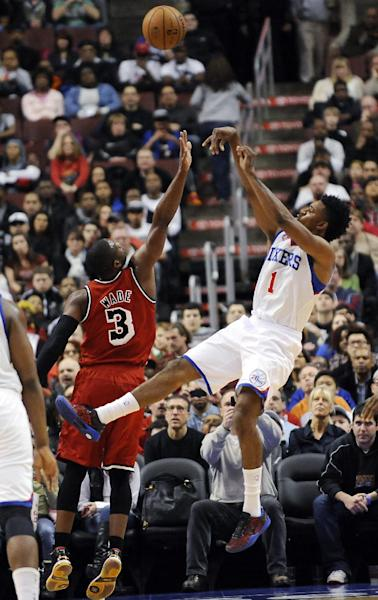 Philadelphia 76ers' Nick Young (1) shoots over Miami Heat's Dwyane Wade (3) during the first half of an NBA basketball game, Saturday, Feb. 23, 2013, in Philadelphia. (AP Photo/Michael Perez)