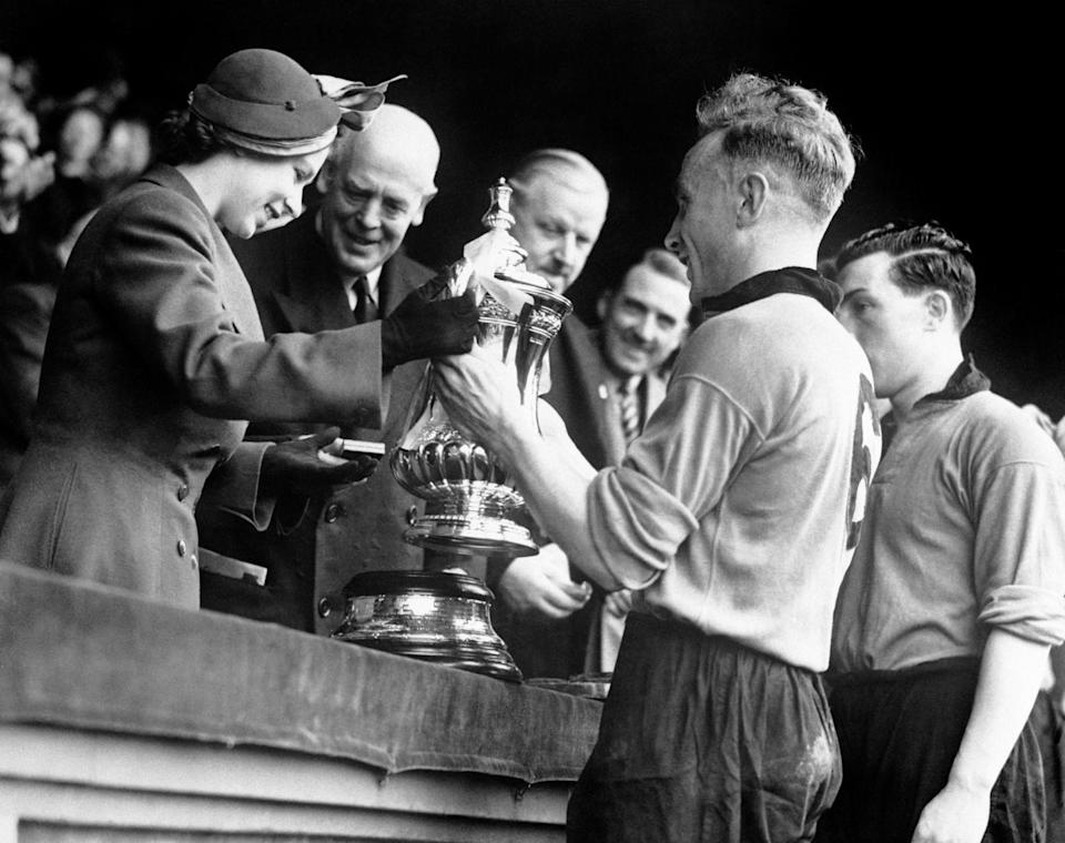 <p>Princess Elizabeth presents the Football Association Cup to Billy Wright, captain of Wolverhampton Wanderers (PA Archive) </p>