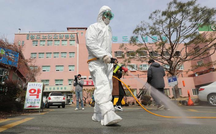 Image: A South Korean health official sprays disinfectant in front of a hospital where a total of 16 infections have now been identified with the COVID-19 coronavirus, in Cheongdo county near the southeastern city of Daegu