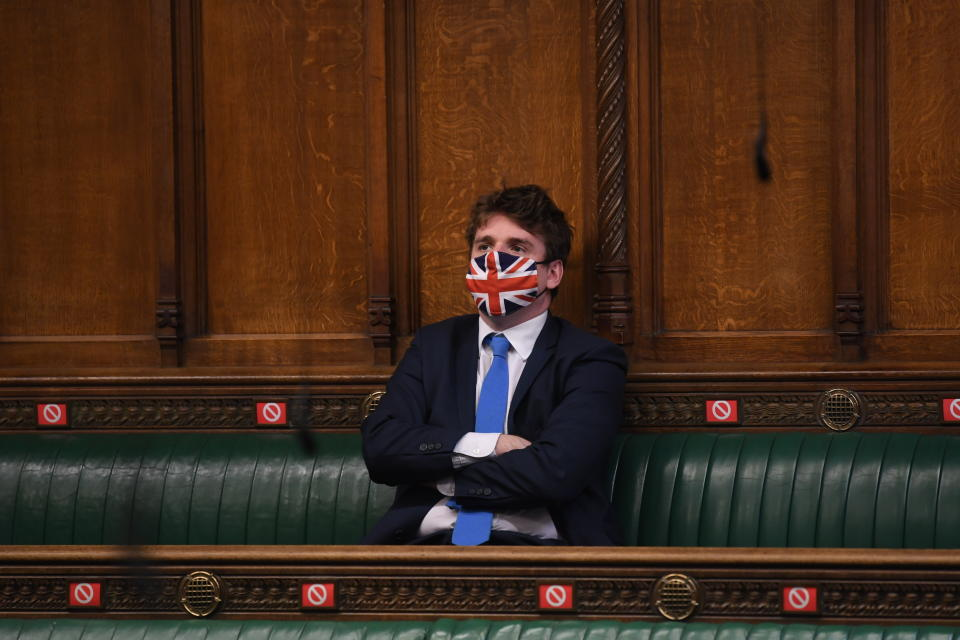 <p>In this handout photo provided by UK Parliament, a member of Parliament looks on wearing a Union Jack face mask to curb the spread of the coronavirus, during Prime Minister's Questions in the House of Commons in London, Wednesday, Feb. 10, 2021. (Jessica Taylor/UK Parliament via AP)</p>