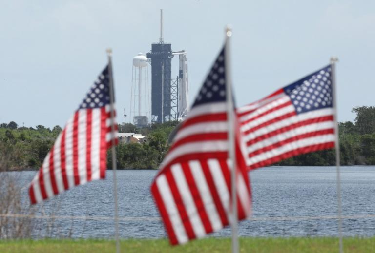 A SpaceX Falcon 9 rocket with the Crew Dragon spacecraft looms in the distance at launch complex 39A as American flags flutter in the wind, at the Kennedy Space Center in Florida on May 29