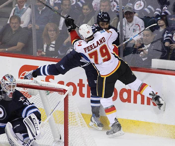 Michael Ferland (front) of the Calgary Flames and Dustin Byfuglien of the Winnipeg Jets collide during third period action in an NHL game at the MTS Centre on April 11, 2015 in Winnipeg, Manitoba, Canada (AFP Photo/Marianne Helm)