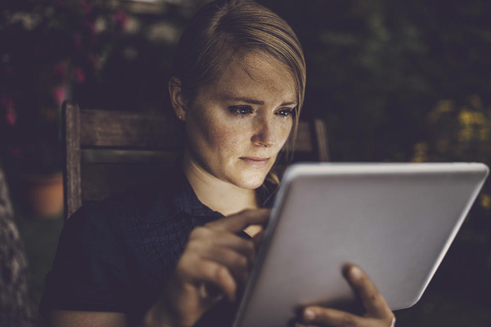 Blondhaired woman using smart device in garden, face is lit by the tablet screen.