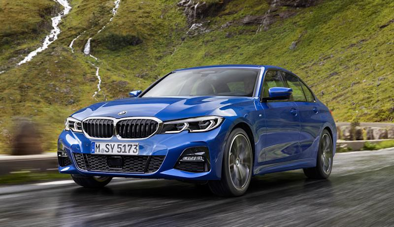 A blue 2019 BMW 3 Series, a compact luxury sedan, on a mountain road in rainy weather.