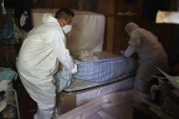 Public funeral service workers remove the body of Amelia Dias Nascimento, 94, who died from complications related to COVID-19 in her home, in Manaus, Amazonas state, Friday, Jan. 22, 2021. The number of people who die in their homes amid the new coronavirus pandemic is growing due to the lack of availability in hospitals and the shortage of oxygen. (AP Photo/Edmar Barros)