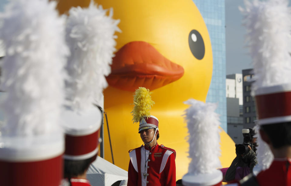 A school marching band leader waits in the heat to perform for the arrival of a giant yellow duck in the port of Kaohsiung, Taiwan, Thursday, Sept. 19, 2013. Despite the heat, thousands flocked to the port of Kaohsiung, the first leg of the Taiwan tour, to see Dutch artist Florentijn Hofman's famous 18 meter (59 foot) yellow duck, a gigantic version of the iconic bathtub toy used by children around the world. (AP Photo/Wally Santana)