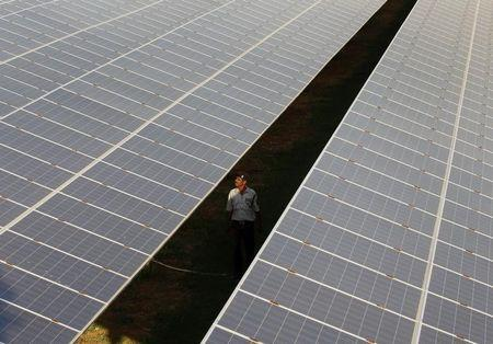 A private security guard walks between rows of photovoltaic solar panels inside a solar power plant at Raisan