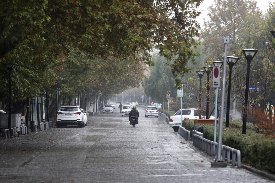 Vehicles drive in an empty street by Iran's main business and trade hub, in Tehran, Satuday, Nov. 21, 2020. Iran on Saturday shuttered businesses and curtailed travel between its major cities, including the capital of Tehran, as it grapples with the worst outbreak of the coronavirus in the Mideast region. (AP Photo/Vahid Salemi)