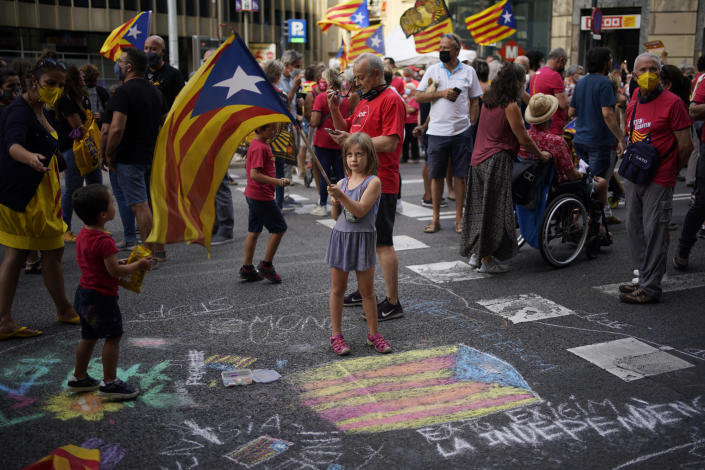 A girl waves a pro-independence flag as demonstrators march during the Catalan National Day in Barcelona, Spain, Saturday, Sept. 11, 2021. Thousands of Catalans have rallied for independence from the rest of Spain in their first major mass gathering since the start of the pandemic. The march in Barcelona on Saturday comes before a meeting between regional leaders in northeast Catalonia and the Spanish government. ( AP Photo/Joan Mateu Parra)
