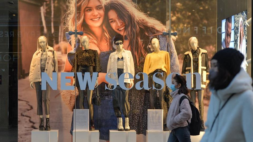 people wearing masks walk past a Topshop shop window
