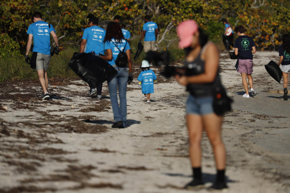 People gather trash on the beach for the Huddle for 100 beach clean up at the Historic Virginia Key Beach Park on Tuesday, Jan. 28, 2020, in Miami. Climate change poses a threat to South Florida's way of life, including Miami's customary spot in the NFL's Super Bowl rotation. The game will be played Sunday in Miami for the 11th time, the most of any city. But the sea and temperature are rising, which could eventually make South Florida an unsuitable Super Bowl site.(AP Photo/Brynn Anderson)