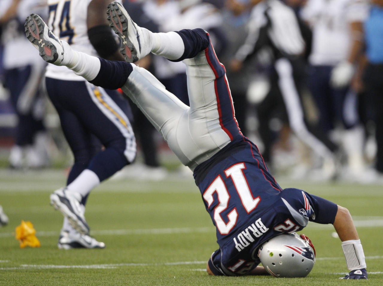 New England Patriots quarterback Tom Brady (12) flips over on his head after he was hit hard by San Diego Chargers defensive tackle Cam Thomas, not seen, in the second half of an NFL football game in Foxborough, Mass., Sunday, Sept. 18, 2011. (AP Photo/Charles Krupa)