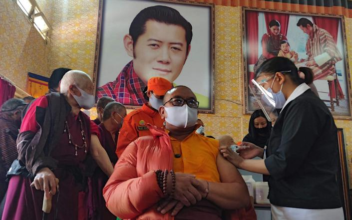 A health worker inoculates a Buddhist monk sitting in front of a portrait of Bhutan's King Jigme Khesar Namgyel Wangchuck in Bhutan - AFP