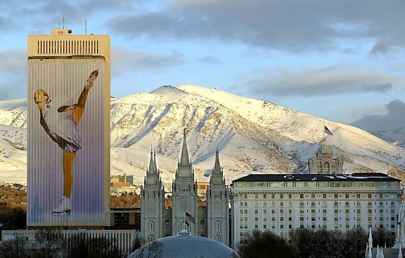 SALT LAKE CITY, UNITED STATES: Downtown Salt Lake City is bathed in the evening sunlight as an Olympic sports banner drapes the 26 story Mormon church office building with the mormon temple in the center during the evening of 23 January, 2002. The 2002 Winter Olympics will open in Salt Lake City in a little more than two weeks. AFP PHOTO/ George Frey (Photo credit should read GEORGE FREY/AFP/Getty Images)
