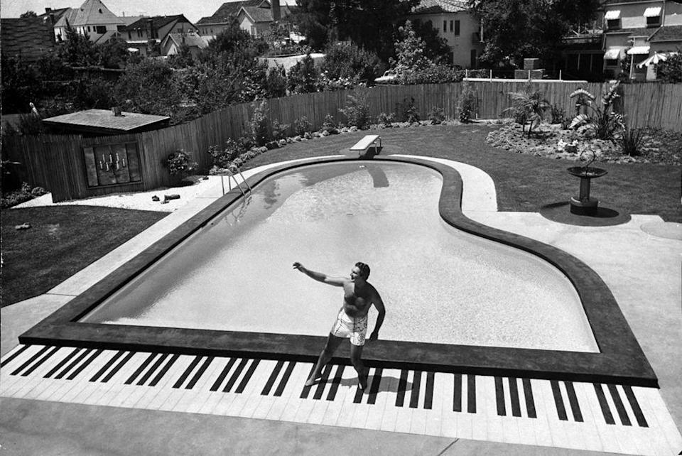 <p>Liberace enjoys the piano-shaped pool at his home in 1954.</p>