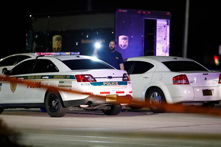 An FBI official investigates the scene of a shooting, Thursday, Dec. 5, 2019, in Miramar, Fla. Four people, including a UPS driver, were killed Thursday after robbers stole the driver's truck and led police on a chase that ended in gunfire at a busy Florida intersection during rush hour, the FBI said.