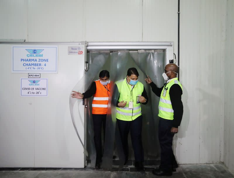 Ground staff exit a temperature-controlled storage room at a cargo terminal of the Indira Gandhi International Airport