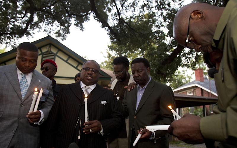 The Rev. Ronald Smith, second from left, leads a prayer during a vigil for shooting victim Brian Claunch Tuesday, Sept. 25, 2012, in Houston. Claunch, a wheelchair-bound double amputee living in a group home for the mentally ill, was shot and killed by Houston Police in the early morning hours Saturday. Police say HPD officer Matthew Martin shot and killed Claunch, who was waving an object in his hand that turned out to be a pen. (AP Photo/Houston Chronicle, Brett Coomer)