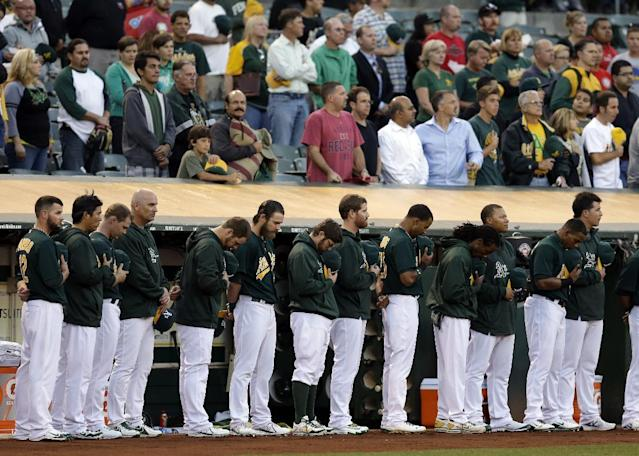 Oakland Athletics and fans hold a moment of silence prior to the baseball game against the Los Angeles Angels in memory of those who lost their lives during today's Navy Yard shooting Monday, Sept. 16, 2013, in Oakland, Calif. (AP Photo/Ben Margot)