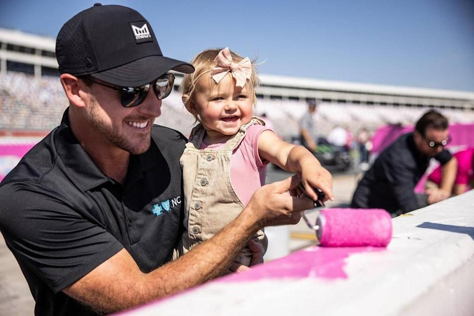 Daniel Hemric, left, holds his daughter, Rhen, while she paints during the Paint Pit Wall Pink event at the Charlotte Motor Speedway in Charlotte, N.C., on Tuesday, September 28, 2021.