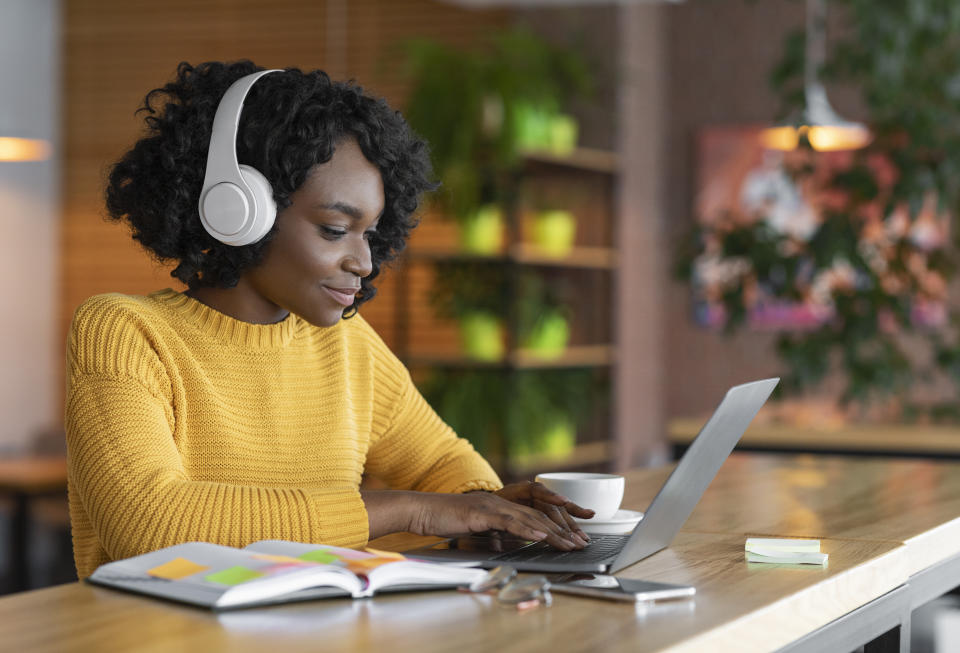 Young afro woman having online training, using laptop and wireless headset at cafe, free space